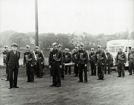 A black and white photograph of a group of men outside, standing in rows, wearing mine rescue gear. They each have a pack on their backs, with tubes going to a face mask resting below their necks and wearing a hat with a light on the front. A man in a suit is standing in front of the group, looking at the camera. The photo is circa 1943.