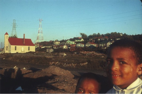 A person posing for the camera with the Africville Chrurch in the background.