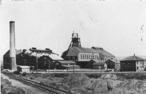 A black and white photograph of the main buildings of the Allan Mine, undated. It shows a large smokestack in front of two two and one half storey buildings, a pithead frame, and three sets of railway tracks, one having box cars and a flatcar.