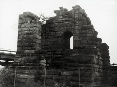 A black and white photograph of the ruin of the Cornish pumphouse, erected by the General Mining Association in 1866 to house the pumping mechanism for the Foord pit. The ruin is made of sandstone blocks and an arched opening is still in place. The photograph was taken in 1987, prior to the dismantling of the ruin.