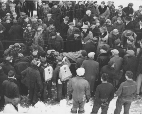A crowd is gathered around bodies (covered with blankets) on stretchers being removed from the McGregor Mine, Jan. 14, 1952. Draegermen, wearing their oxygen packs can be seen.