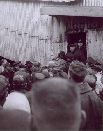 Black and white photograph taken over the heads of a crowd watching a stretcher containing a body that is not clearly seen, leaving a metal-sided building. From the Springhill Disaster of 1 November 1956.