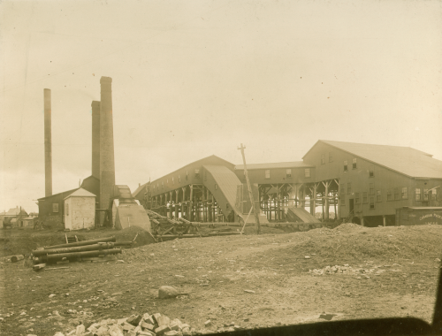 Sepia-coloured photograph showing surface buildings and smokestacks of a coal mine, including the covered slope into the mine. This is the Cumberland Railway & Coal Company Colliery, West Slope, Springhill, Cumberland County. Burke W. Weston? photographer. Nova Scotia Museum: P119.118.