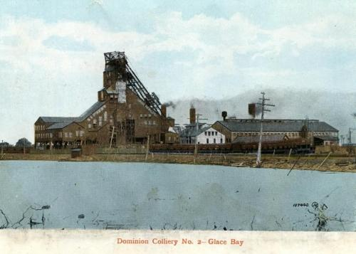 : Postcard of the surface buildings of No. 2 Colliery in Glace Bay, 1912. There is a pond in the foreground and smoke coming from a chimney. The bankhead is featured prominently.