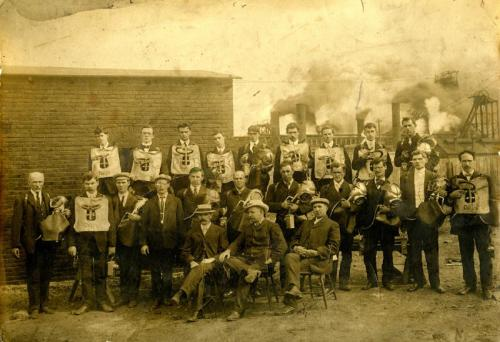 A sepia-toned photograph of a large group of men. Most are wearing a protective chest plate or breathing bag, some are holding helmets, and others have pieces of equipment. They are wearing suits. Three men are sitting in front, all wearing hats. In the background are several smokestacks billowing black smoke.