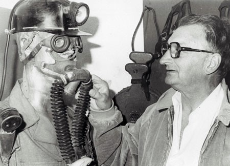 A black and white photograph of draegerman Robert Hoegg pointing out the pieces of his mine rescue equipment on a mannequin, circa 1980. The equipment included a mine helmet with light, goggles, an oxygen mask over the mouth, a nose clip and tubes leading to a pack that is not in the photo.