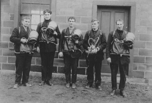 An undated black and white photograph of a group of 5 men wearing suits and their draeger equipment. They have breathing bag pouches in front with breathing tubes attached and are holding metal helmets.