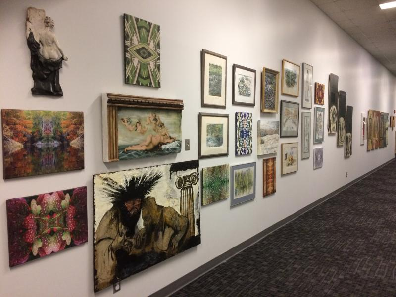 A variety of artwork displayed in a hallway