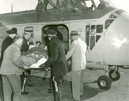 A black and white photograph of two RCMP officers and a few other men handling a stretcher containing a man wrapped in blankets being loaded into the open door of a helicopter.
