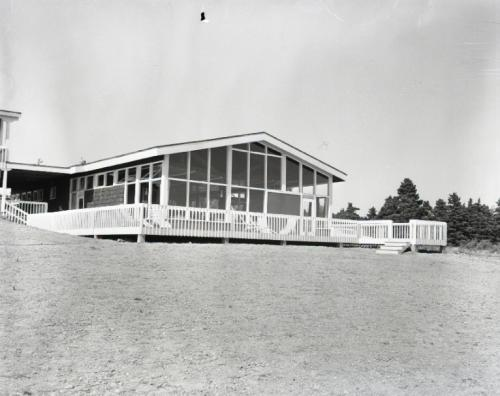 A black and white photograph taken in 1960 of one of the three buildings comprising the new Silver Dart Motel in Baddeck. The photo was taken from the front of the property. The photo was taken by Abbass Studios and is courtesy of the Beaton Institute of Cape Breton University, Reference Number: A-6051.