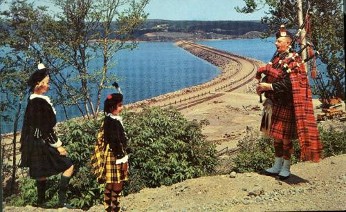 "A colour postcard of the Canso Causeway in the background, with a Scottish bagpiper playing the pipes and two girls in Scottish kilts and tams on a hill above. This was a common Cape Breton tourism promotional image in the 1960s. The postcard title is ""The Road To The Isles Causeway""."