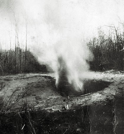 : A black and white photograph showing a small  explosive cloud near ground level. It is said that this was methane gas spontaneously escaping from the ground in Pictou County.