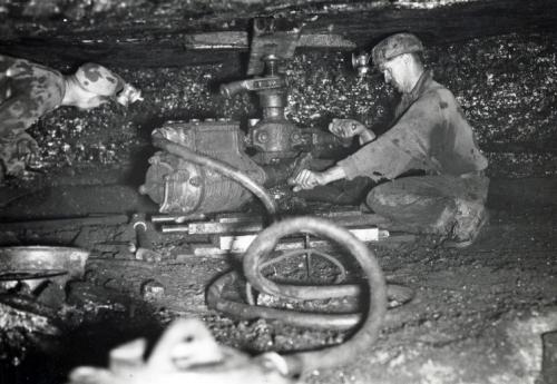 A black and white photography circa 1940 of a miner crouching beside a coal shearer, hands on the controls, roof close to his head.