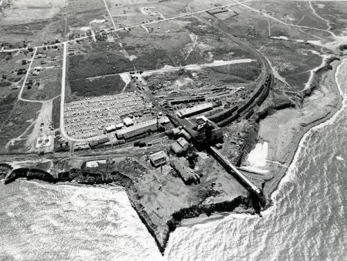 : A modern black and white photograph of an aerial view of Number 26 colliery, Glace Bay, 1977, showing its proximity to the Atlantic Ocean.