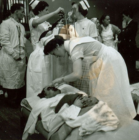 Black and white photograph of a nurse leaning over a man on a stretcher, applying something to his blackened face. Other nurses and a doctor are in the background. This is from the Springhill Mine Disaster, 1 November 1956.