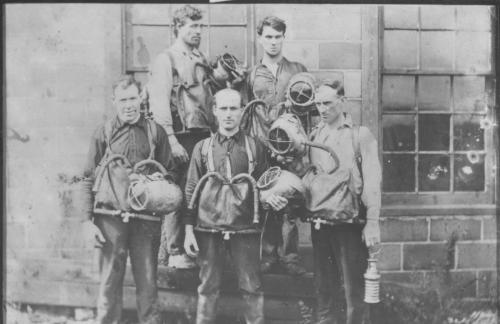 n undated black and white photograph of a group of five unidentified early Pictou County draegermen. They are wearing large pouches in front, held on with straps around their shoulders with two breathing tubes coming from the pouch. Each man is holding a metal helmet, similar to the type used for deep-sea diving. One also is holding a miner's lamp.