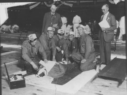 An undated black and white photograph of a mine rescue competition. A group of men all dressed alike are on their knees attending to a man laid out on the floor. They have bandaged his head, arm and leg. In the background can be seen other groups engaged in similar activities.