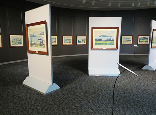 A colour photograph of an exhibit gallery with several watercolour paintings in wooden frames hanging in a row on a dark grey wall. In the foreground are free-standing units, each with a watercolour painting hanging on it. This is a photograph of the Museum's temporary exhibit called the Silver Dart collection. The artist is Joseph Purcell. The watercolours are of Cape Breton landscape scenes, commissioned in 1960 for Baddeck's Silver Dart Motel.