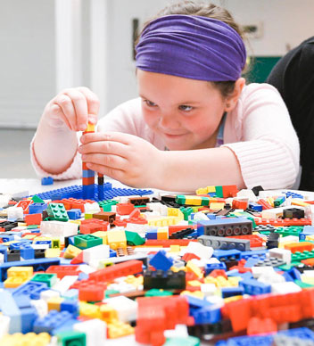A colour photograph of a girl sitting at a table building something with Lego blocks. In front of her, the table is full of colourful Lego blocks.