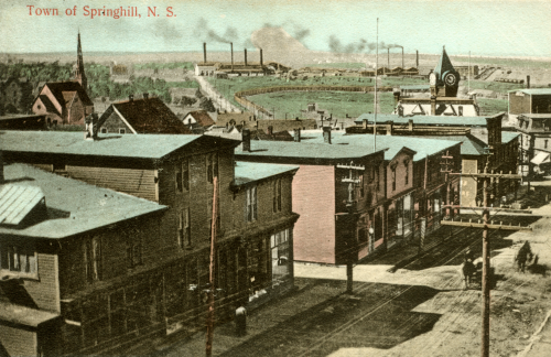 A hand-coloured postcard of the buildings on the main downtown street of Springhill, with the smokestacks and buildings of two coal mines seen in the distance. The postcard is undated.