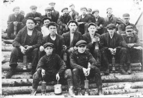 a black and white photograph of a group of 22 Vale Colliery miners from Thorburn. It includes both men and boys, sitting on a pile of logs that will be used for pit timbers.They are holding mine lamps and piece cans - which are lunch buckets - circa 1910.