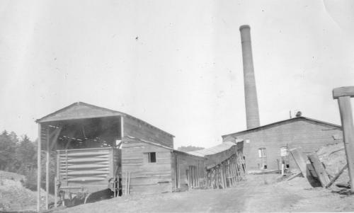 Black and white photograph showing buildings of the Victoria Mine in River Hebert, including a rail car in an enclosure, a covered long, narrow building on stilts (possibly to protect a conveyor or mine trip) and a smokestack behind a non-descript building. The photo is undated.