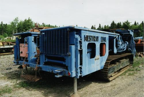 A colour photograph of a large piece of machinery, painted blue. On the side of the machine are letters spelling Westray Coal.