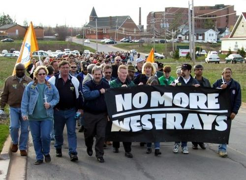 A colour photograph circa the 1990s, of a large group marching down a New Glasgow street, some carrying flags. Those in front carry a large black banner with white letters reading No More Westrays.