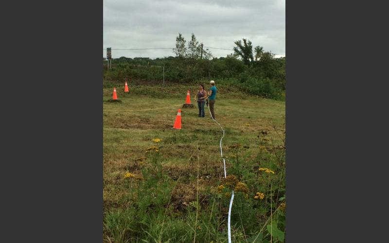 Using measuring tapes to layout the dig site and find the location of the last dig in 1992.
