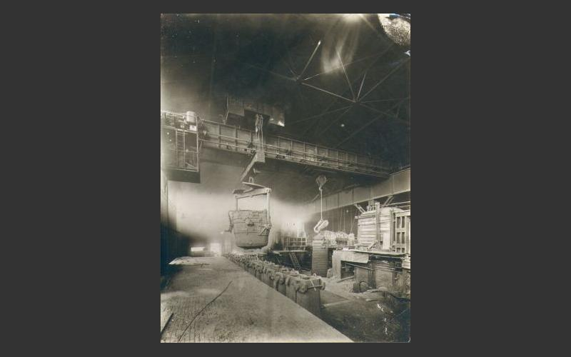Here a ladle (bucket) moves over a row of ingot moulds in the Sydney steel plant, pouring molten steel into their open tops. Once the steel cools, the moulds are lifted off with a crane, leaving an ingot. An ingot is a chunk of steel that gets processed further into steel products, such as railway rails, wire, nails and locomotive axles.