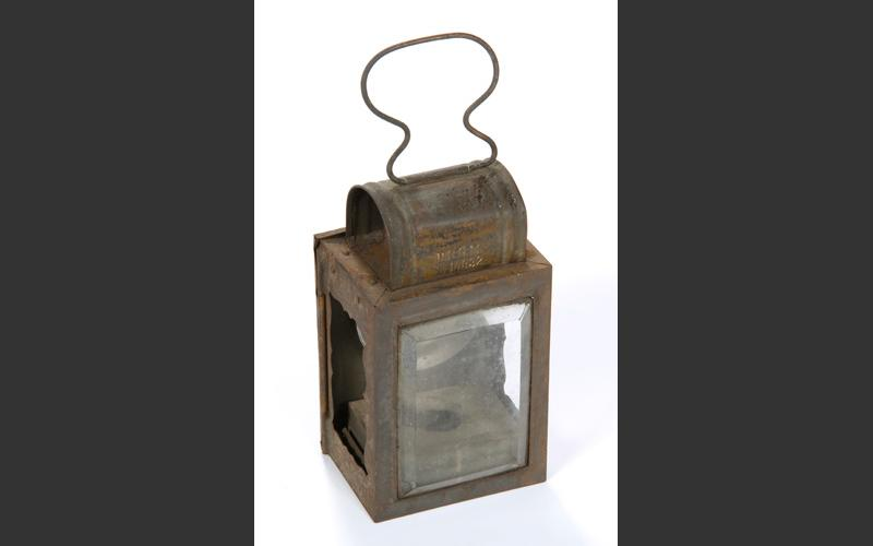 A candle lamp: this was the lighting used in the mines before the development of enclosed kerosene lamps.