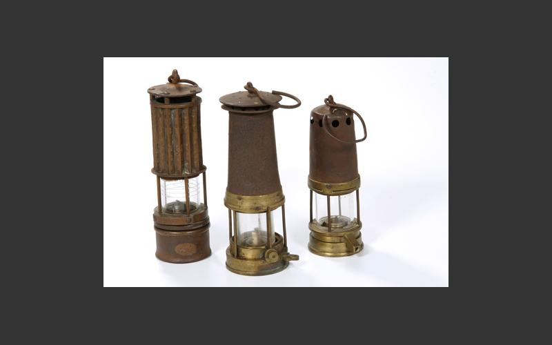 Three kerosene safety lamps. These lamps provided light and also monitored air quality. Their development began in the early nineteenth century and they were in use into the early twentieth century, gradually replaced by electric lights.