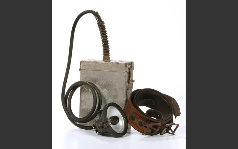 Electric head lamp with battery pack and leather belt. These became standard equipment in the postwar years and are still in use in modern mines. The lamp hooks onto the front of the miner's hardhat.