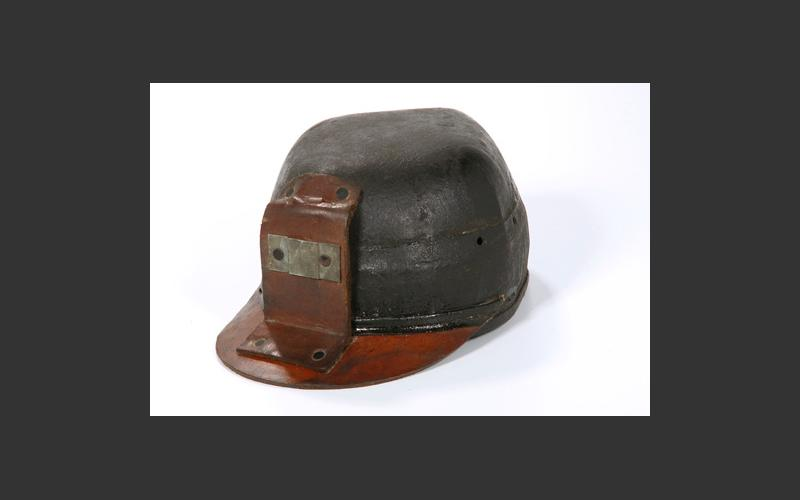 Early version of a miner's hard hat. It has the mount on the front for his lamp.