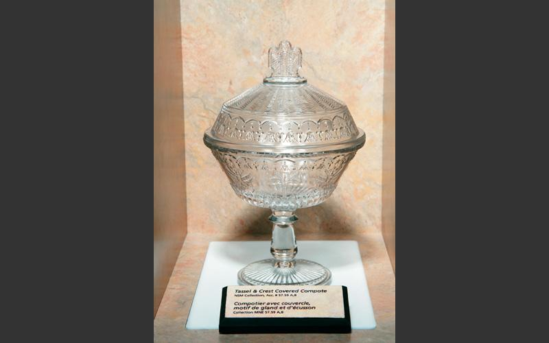 A pressed glass compote on display with goblets, kerosene lamp shades and plates. Nova Scotia had a short-lived pressed glass industry based in Trenton, N.S.