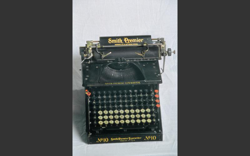 A Smith Premier No. 10 manual typewriter with full keyboard. The black keys type uppercase and the white keys type lowercase letters. This model was introduced in 1908 and was the primary tool for clerical work. Not currently on display