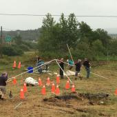 A tent going up to provide shelter for the dig. Small stumps left from clearing the land were marked by orange pylons so trip hazards could be avoided.