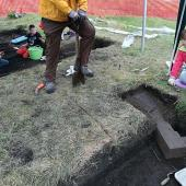 The archaeologist marks the area of sod he will remove.
