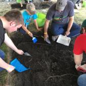 Participants used trowels to dig dirt, small brooms to brush, dustpans to lift dirt into the green trugs that were then taken to a sifter.