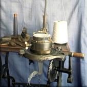 A table-mounted knitting machine for making socks. Built on the same principles as large industrial machines, these small versions were marketed to housewives as a way to make money at home.